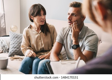 Photo of unhappy annoyed couple man and woman having conversation with psychologist on therapy session in room