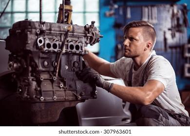 Photo of uniformed car technician maintaining automotive engine