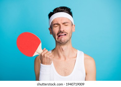 Photo of unsatisfied person hand hold ping pong racket closed eyes grimace cry isolated on blue color background
