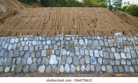 Photo of unstable mound underneath built by stone walls to erosion barrier.