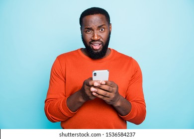 Photo of unsure man mixed-race looking at you with arrogance holding telephone browsing through this to find truthful information isolated vivid color blue background