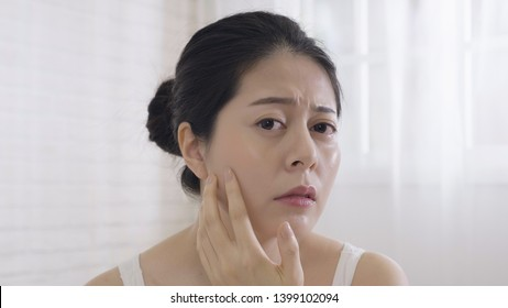 Photo upset asian woman squeezing pimple on face while standing on white background copy space. young elegant wife resting at home looking camera as mirror checking cheek frowning unhappy dry skin