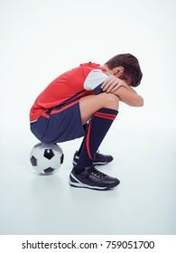 Photo of upset  teen boy in sportswear after soccer game - posing at studio