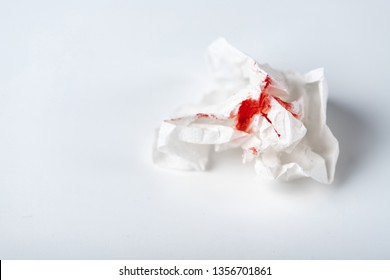 A photo of used bloody toilet paper on the light blue background. Menstrual or hemorrhoids bleeding