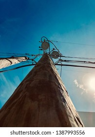 Photo of a utility power pole designed for providing electricity for the city with the blue sky without clouds and sun shining as its background
