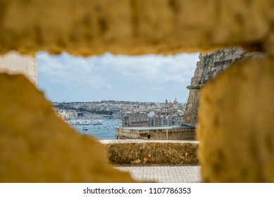 Photo of Valletta, Malta, view behind hole in ancient wall