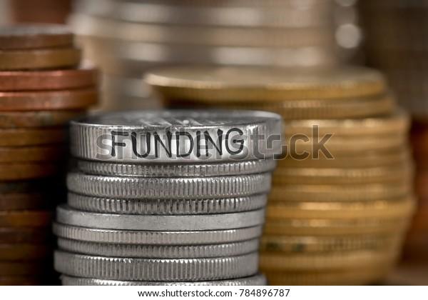 Photo de diverses piles et rangées de pièces de monnaie avec mot de concept de FINANCEMENT imprimé sur la surface métallique