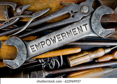 Photo of various tools and instruments with EMPOWERMENT letters imprinted on a clear wrench surface