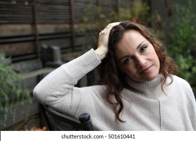 Photo of a very attractive 40-year-old woman with brown hair and eyes. She is sitting in her back yard on a cool fall morning.