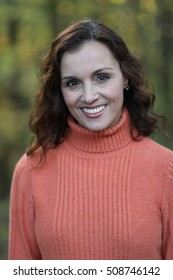 Photo of a very attractive 40-year-old woman with brown hair and eyes. She has a fall forest in the background that has been shot out of focus with lots of bokeh.