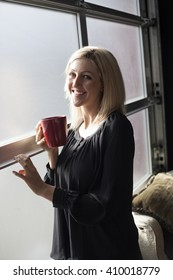 Photo of a very attractive blonde in a black shirt holding a red coffee cup and standing by a window.