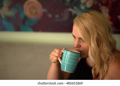 Photo of a very attractive blonde in a black top drinking coffee from a blue cup.