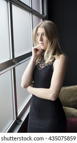 Photo of a very attractive blonde in a sexy black dress looking out a window at a party.