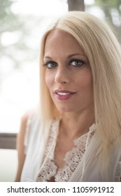 Photo of a very attractive blonde woman with beautiful blue eyes. She is wearing a white, sleeveless blouse.