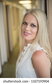 Photo of a very attractive blonde woman with beautiful blue eyes. She is wearing a white, sleeveless blouse and standing in a doorway.