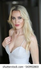 Photo of a very attractive blonde woman with beautiful green eyes wearing a white wearing a low cut white gown.