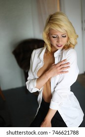 Photo of a very attractive blonde woman with beautiful blue eyes. She is looking away from the camera and wearing a white shirt.
