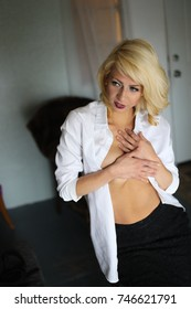 Photo of a very attractive blonde woman with beautiful blue eyes. She is looking straight at the camera and wearing a white shirt.