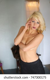 Photo of a very attractive blonde woman with beautiful blue eyes. She is looking straight at the camera and is topless.
