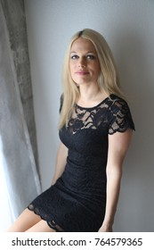 Photo of a very attractive blonde woman with beautiful blue eyes. She is wearing a short, lacy black dress.
