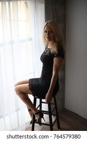 Photo of a very attractive blonde woman with beautiful blue eyes. She is wearing a short, lacy black dress. She is sitting on a stool in front of a large window.