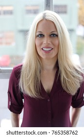 Photo of a very attractive blonde woman with beautiful blue eyes. She is wearing a purple top and is standing by a window.