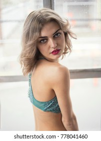 Photo of a very attractive blonde woman with beautiful blue eyes. She is looking straight at the camera and wearing a turquoise halter top.