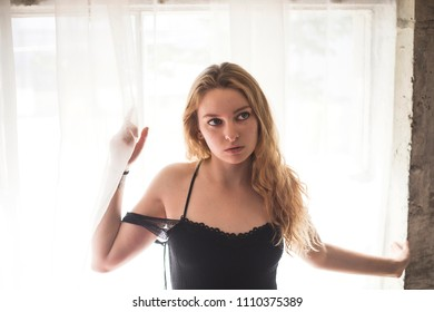 Photo of a very attractive redhead wearing a black dress and standing in front of a window with sheer white curtains.