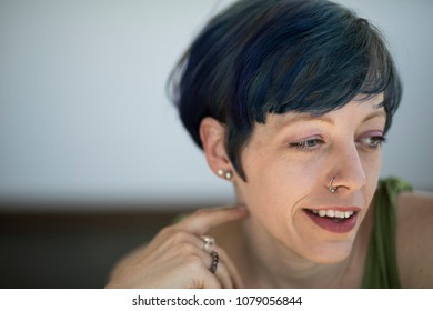 Photo of a very attractive woman with beautiful blue eyes and blue hair. She is looking away from the camera and wearing a pretty green top.