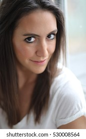 Photo of a very attractive young woman with brown hair and eyes. She is wearing a white tee shirt.