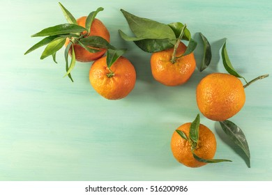 A photo of vibrant orange tangerines with green leaves, shot from above on a light background texture with copyspace