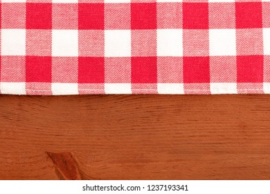 A photo of a vichy pattern cloth on a dark rustic wooden background, an abstract restaurant frame with copy space