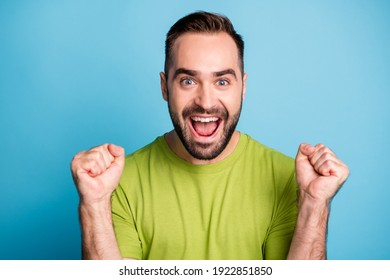 Photo of victorious happy man raise fists wear green t-shirt isolated on pastel blue color background
