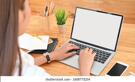 Photo views from back of young woman while using/typing on white blank screen laptop including pencil holder, black blank screen smartphone, potted plant, pencil, notes, earphone on wooden desk.