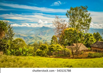 Photo of village house with wooden fence and high mountains in distance in Sara village and Mt. Michael in Papua New Guinea.