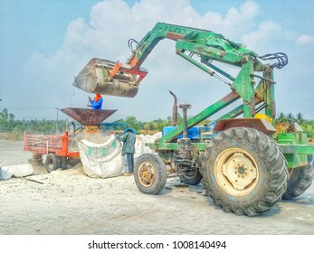 Photo of villager filling big bag by their low technology way, using tractor to lift the bag up and grind to small pieces by their homemade machine