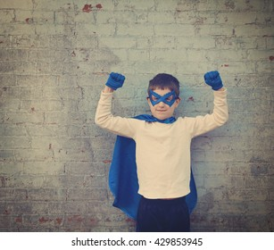 A photo of a vintage child dressed up as a super hero with his strong arms up for a confidence, bravery or imagination concept.