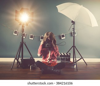 A photo of a vintage child taking a picture with an old camera in a studio with lights and film for a creativity or vision concept.