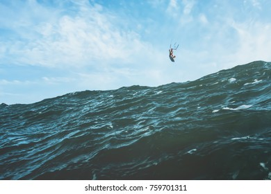 Photo with a vintage look of a surfer jumping over a gigantic wave
