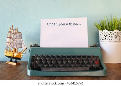photo of vintage typewriter with phrase: ONCE UPON A TIME, on wooden table