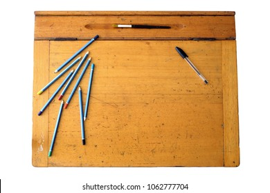 A photo of a vintage wooden school desk, featuring a hinged lid and pen/pencil groove, and with some coloured pencils, paint bush and a pen.