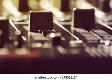 Photo of volume sliders on a sound mixer controller.Vintage look.