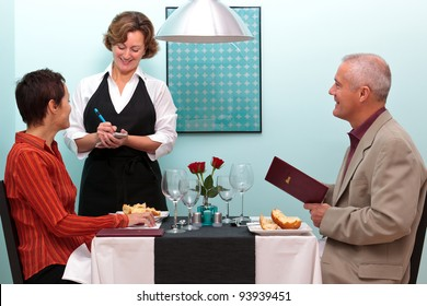 Photo of a waitress in a restaurant taking a food order from a mature couple who are sat at a table.