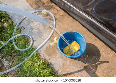 photo of water hose and yellow sponge in blue bucket for car wash at house parking lot