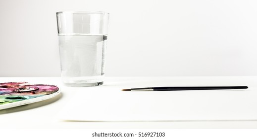 A photo of a watercolor brush, with a palette, a water glass in the blurred background, and a blank sheet of paper with plenty of copyspace