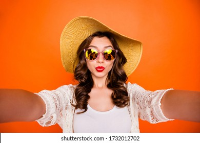 Photo of wavy cheerful cute sweet pretty white girlfriend taking sefie pouting lips on vacation isolated over vivid color orange background