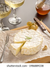 In the photo, we see white wine served with camembert cheese