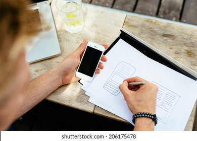 Photo of a web designer drawing a blueprint of a new mobile application