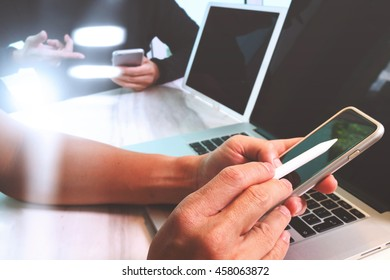 Photo website graphic designer hand working with his team make new project in studio.Modern laptop extend screen digital tablet smart phone on wood table. sun flare effect