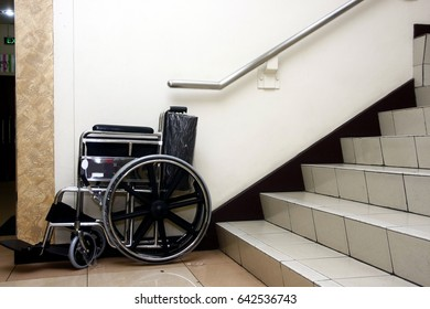 Photo of a wheelchair parked at the bottom of a set of staircase.